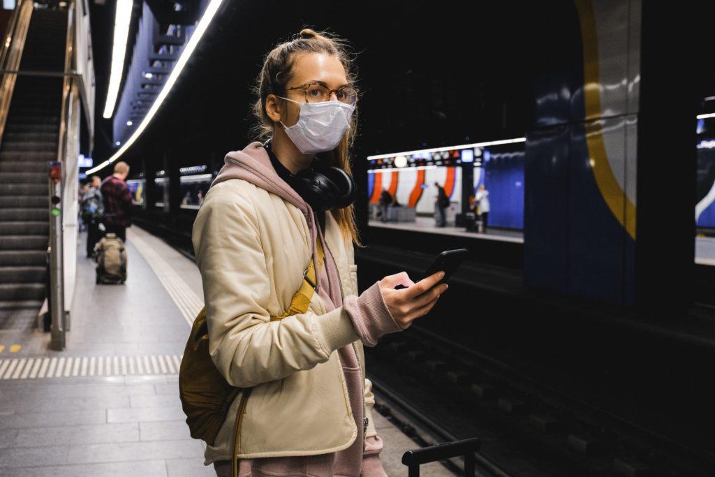 woman in beige coat wearing black headphones 3943952